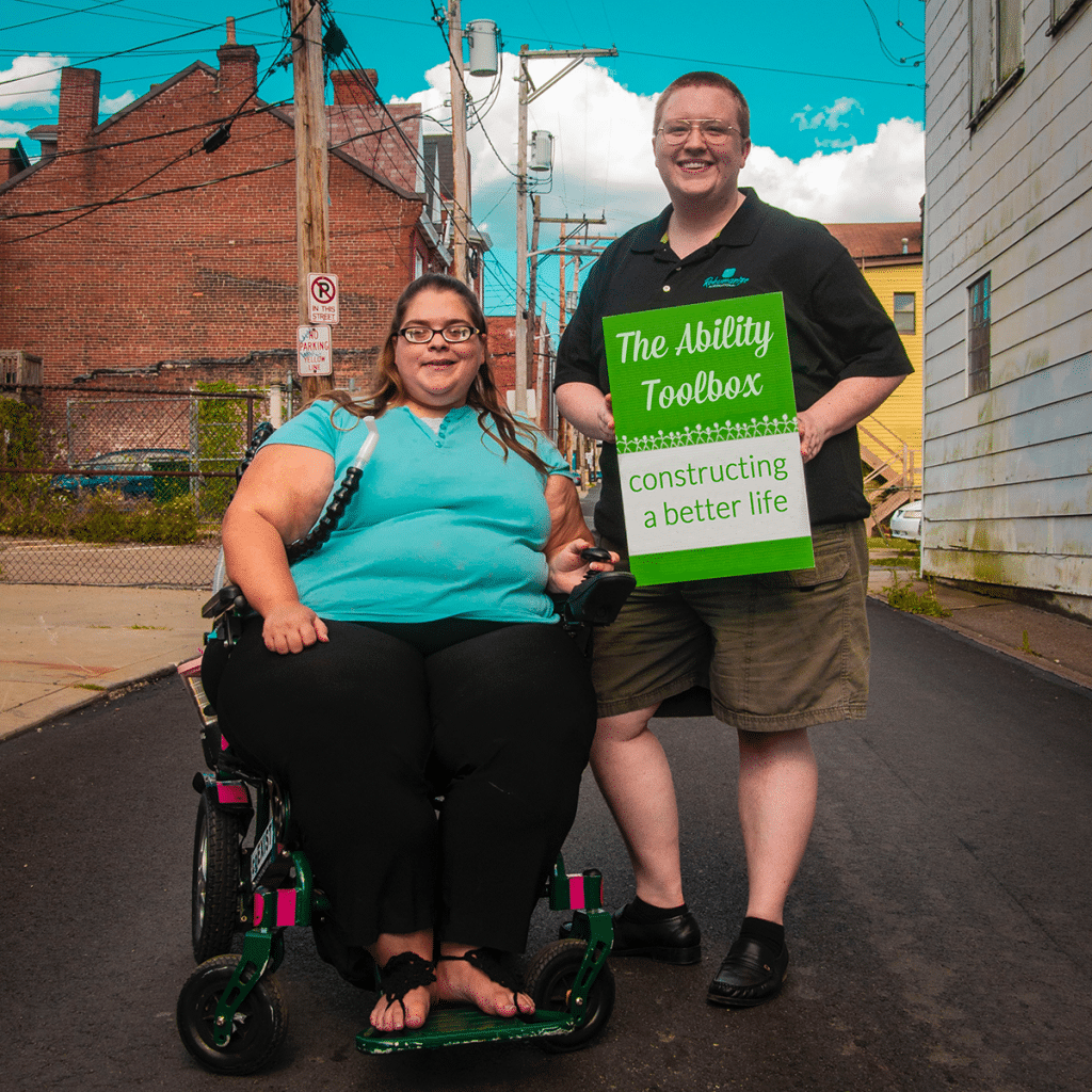 Woman in a wheelchair and friend holding sign that reads: The Ability Toolbox. Constructing a better life.