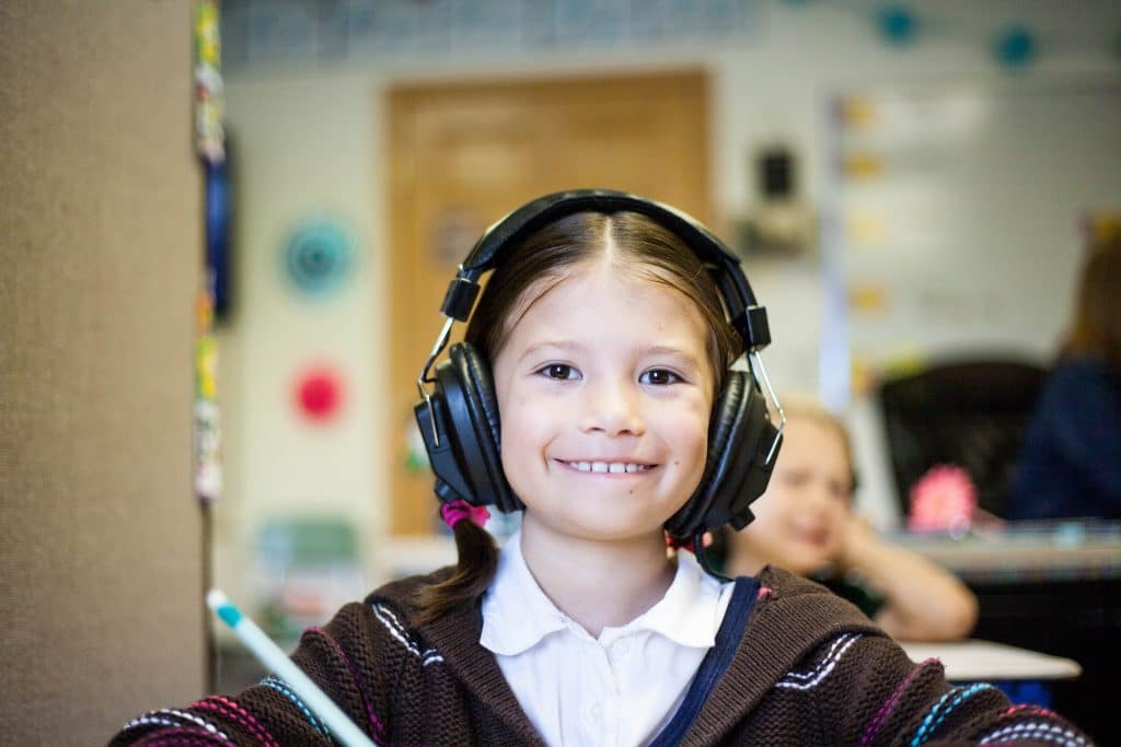 Smiling girl with autism noise canceling headphones