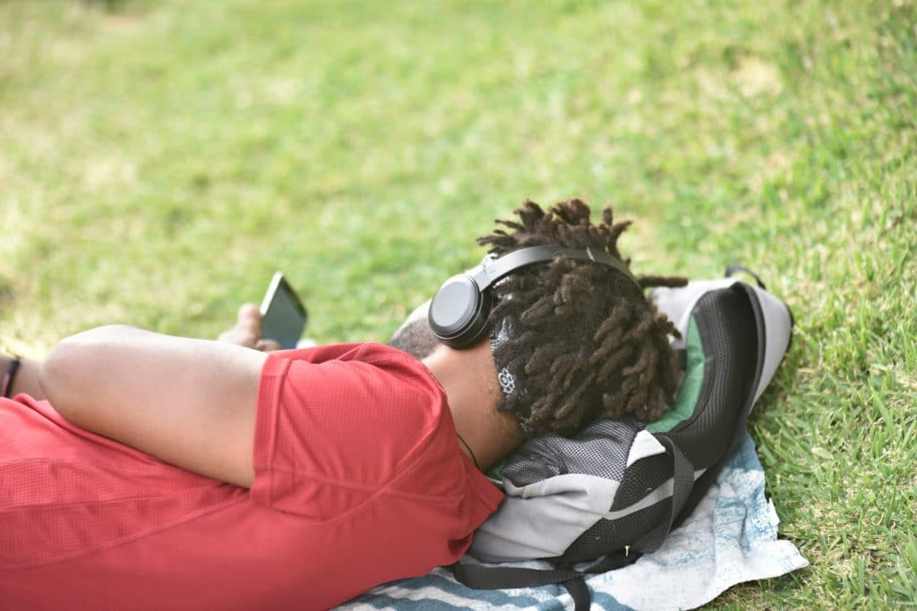 Black man laying in the grass wearing autism noise canceling headphones
